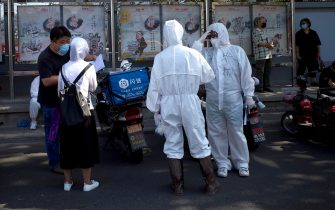Medical staff members in full protective gear stand outside the Guangan sports centre to assist people who live near or who have visited the Xinfadi Market, a wholesale food market where a new COVID-19 coronavirus cluster has emerged, for testing in Beijing on June 16, 2020. - China reported another 27 domestically transmitted coronavirus cases in Beijing, where a fresh cluster linked to a wholesale food market has sparked WHO concern and prompted a huge trace-and-test programme. (Photo by Noel Celis / AFP) (Photo by NOEL CELIS/AFP via Getty Images)