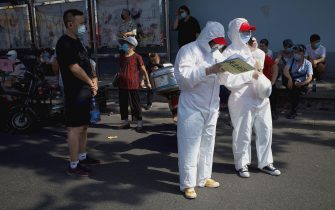 TOPSHOT - Medical staff members in full protective gear stand outside the Guangan sports centre to assist people who live near or who have visited the Xinfadi Market, a wholesale food market where a new COVID-19 coronavirus cluster has emerged, for testing in Beijing on June 16, 2020. - China reported another 27 domestically transmitted coronavirus cases in Beijing, where a fresh cluster linked to a wholesale food market has sparked WHO concern and prompted a huge trace-and-test programme. (Photo by Noel Celis / AFP) (Photo by NOEL CELIS/AFP via Getty Images)