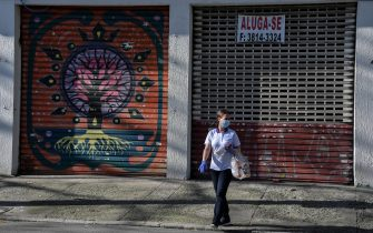 A woman walks past an empty store to rent in a comercial area of Sao Paulo, Brazil, on June 17, 2020. - Sao Paulo is resuming its economic activity, but in some streets of Brazil's largest metropolis a succession of low iron curtains is evidence of the impact of the coronavirus: merchants have closed down. (Photo by NELSON ALMEIDA / AFP) (Photo by NELSON ALMEIDA/AFP via Getty Images)