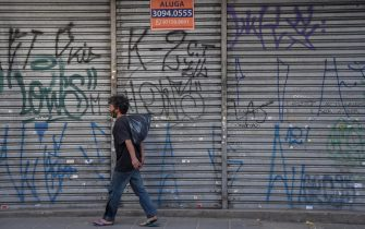 A homeless walks past an empty store to rent in a comercial area of Sao Paulo, Brazil, on June 17, 2020. - Sao Paulo is resuming its economic activity, but in some streets of Brazil's largest metropolis a succession of low iron curtains is evidence of the impact of the coronavirus: merchants have closed down. (Photo by NELSON ALMEIDA / AFP) (Photo by NELSON ALMEIDA/AFP via Getty Images)