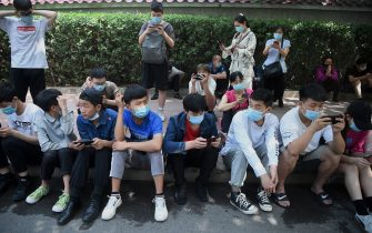 Young people look at their phones while waiting to take a swab test for the COVID-19 coronavirus as officials conduct mass testing following a new cluster of cases last week, in Beijing on June 18, 2020. - Beijing reported another 21 cases of the coronavirus on June 18, as authorities rushed to contain a new outbreak in the capital and warned cases may keep rising. (Photo by Noel Celis / AFP) (Photo by NOEL CELIS/AFP via Getty Images)