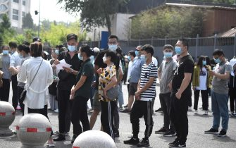 People wearing face masks wait to take a swab test for the COVID-19 coronavirus as officials conduct mass testing following a new cluster of cases last week, in Beijing on June 18, 2020. - Beijing reported another 21 cases of the coronavirus on June 18, as authorities rushed to contain a new outbreak in the capital and warned cases may keep rising. (Photo by Noel Celis / AFP) (Photo by NOEL CELIS/AFP via Getty Images)