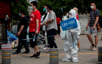 A member of the medical staff in full protective gear holds up a sign to assist people who live near or who have visited the Xinfadi Market, a wholesale food market where a new COVID-19 coronavirus cluster has emerged, as they arrive for testing in Beijing on June 17, 2020. - Beijing's airports cancelled two-thirds of all flights and schools in the Chinese capital were closed again on June 17 as authorities rushed to contain a new coronavirus outbreak linked to the Xinfadi wholesale food market. (Photo by NOEL CELIS / AFP) (Photo by NOEL CELIS/AFP via Getty Images)