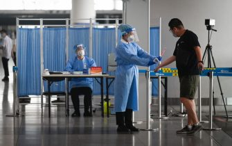 An airport worker wearing protective clothing takes a temperature reading of a man at the Beijing International Airport on June 17, 2020. - Beijing's airports cancelled more than 1,200 flights and schools in the Chinese capital were closed again on June 17 as authorities rushed to contain a new coronavirus outbreak linked to a wholesale food market. (Photo by STR / AFP) (Photo by STR/AFP via Getty Images)