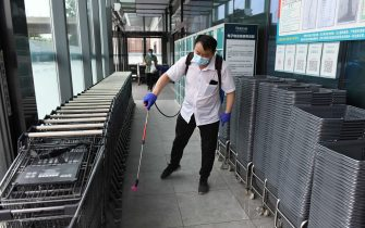 A worker disinfects shopping baskets and carts at the entrance of a supermarket in Beijing on June 17, 2020. - The supermarket has stepped up virus prevention work after a new outbreak of the COVID-19 coronavirus at a wholesale market in Beijing last week. (Photo by GREG BAKER / AFP) (Photo by GREG BAKER/AFP via Getty Images)