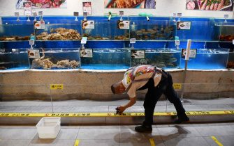 A worker cleans glass in the seafood section of a supermarket in Beijing on June 17, 2020. - The supermarket, which has its own supply chain not linked to the Xinfadi market, has seen a 20 percent increase in online orders since a new outbreak of the COVID-19 coronavirus in Beijing last week. (Photo by GREG BAKER / AFP) (Photo by GREG BAKER/AFP via Getty Images)