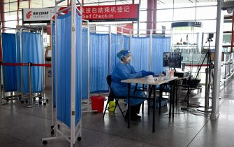 An airport worker wearing protective clothing is seated by a monitor next to a temperature detector at the Beijing International Airport on June 17, 2020. - Beijing's airports cancelled more than 1,200 flights and schools in the Chinese capital were closed again on June 17 as authorities rushed to contain a new coronavirus outbreak linked to a wholesale food market. (Photo by STR / AFP) (Photo by STR/AFP via Getty Images)