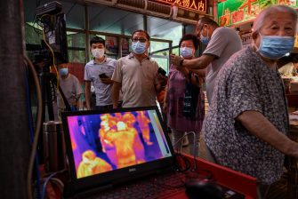 BEIJING, CHINA - JUNE 19: Chinese shoppers have their temperature checked by thermal imaging at the entrance to a local market on June 19, 2020 in Beijing, China. Authorities are trying to manage a COVID-19 outbreak linked to the Xinfadi wholesale food market, Beijing's biggest supplier of produce and meat. Several neighborhoods have been locked down and a number of other food markets closed, as tens of thousands of people are being tested for COVID-19 at sites set up around the city. The outbreak had triggered fears of a second wave of infection after 56 straight days with no domestically transmitted cases in the capital. More than 8,000 vendors and staff at Xinfadi have already been tested, according to city officials, who are using contact tracing to reach an estimated 200,000 people who have visited the market since May 30. (Photo by Kevin Frayer/Getty Images)