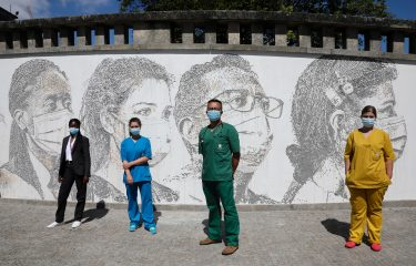 epa08495709 Health workers (L-R), Cristina Teixeira, Raquel Queiros, David Andrade and Idalina Ramos pose in front of their portraits that are part of a mural at Sao Joao Hospital in Porto, Portugal, 19 June 2020. The artwork carved by Portuguese street artist Alexandre Farto, tag-named as VHILS, depicts the faces of ten healthcare workers and is a tribute to all medical and health workers who are looking after those in need amid the ongoing pandemic of the COVID-19 disease caused by the SARS-CoV-2 coronavirus.  EPA/JOSE COELHO