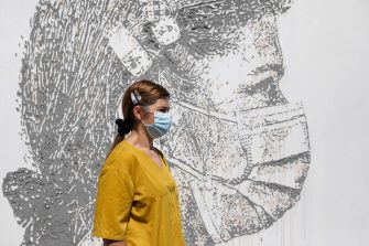 epaselect epa08495707 Health worker Idalina Ramos poses in front of her portrait that is part of a mural at Sao Joao Hospital in Porto, Portugal, 19 June 2020. The artwork carved by Portuguese street artist Alexandre Farto, tag-named as VHILS, depicts the faces of ten healthcare workers and is a tribute to all medical and health workers who are looking after those in need amid the ongoing pandemic of the COVID-19 disease caused by the SARS-CoV-2 coronavirus.  EPA/JOSE COELHO