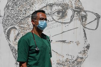epa08495722 Health worker David Andrade poses in front of his portrait that is part of a mural at Sao Joao Hospital in Porto, Portugal, 19 June 2020. The artwork carved by Portuguese street artist Alexandre Farto, tag-named as VHILS, depicts the faces of ten healthcare workers and is a tribute to all medical and health workers who are looking after those in need amid the ongoing pandemic of the COVID-19 disease caused by the SARS-CoV-2 coronavirus.  EPA/JOSE COELHO