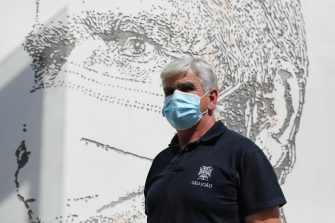 epa08495726 Health worker Manuel Martins poses in front of his portrait that is part of a mural at Sao Joao Hospital in Porto, Portugal, 19 June 2020. The artwork carved by Portuguese street artist Alexandre Farto, tag-named as VHILS, depicts the faces of ten healthcare workers and is a tribute to all medical and health workers who are looking after those in need amid the ongoing pandemic of the COVID-19 disease caused by the SARS-CoV-2 coronavirus.  EPA/JOSE COELHO