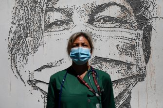 epa08495727 Health worker Maria Joao poses in front of her portrait that is part of a mural at Sao Joao Hospital in Porto, Portugal, 19 June 2020. The artwork carved by Portuguese street artist Alexandre Farto, tag-named as VHILS, depicts the faces of ten healthcare workers and is a tribute to all medical and health workers who are looking after those in need amid the ongoing pandemic of the COVID-19 disease caused by the SARS-CoV-2 coronavirus.  EPA/JOSE COELHO