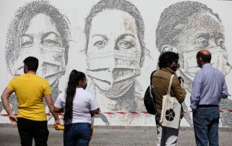 epa08495714 People look at a mural at Sao Joao Hospital in Porto, Portugal, 19 June 2020. The artwork carved by Portuguese street artist Alexandre Farto, tag-named as VHILS, depicts the faces of ten healthcare workers and is a tribute to all medical and health workers who are looking after those in need amid the ongoing pandemic of the COVID-19 disease caused by the SARS-CoV-2 coronavirus.  EPA/JOSE COELHO