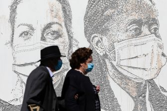 epa08495724 A couple passes by a mural at Sao Joao Hospital in Porto, Portugal, 19 June 2020. The artwork carved by Portuguese street artist Alexandre Farto, tag-named as VHILS, depicts the faces of ten healthcare workers and is a tribute to all medical and health workers who are looking after those in need amid the ongoing pandemic of the COVID-19 disease caused by the SARS-CoV-2 coronavirus.  EPA/JOSE COELHO