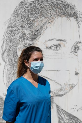 epa08495725 Health worker Patricia Botelho poses in front of her portrait that is part of a mural at Sao Joao Hospital in Porto, Portugal, 19 June 2020. The artwork carved by Portuguese street artist Alexandre Farto, tag-named as VHILS, depicts the faces of ten healthcare workers and is a tribute to all medical and health workers who are looking after those in need amid the ongoing pandemic of the COVID-19 disease caused by the SARS-CoV-2 coronavirus.  EPA/JOSE COELHO