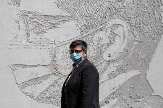 epa08495728 Health worker Paula Guimaraes poses in front of her portrait that is part of a mural at Sao Joao Hospital in Porto, Portugal, 19 June 2020. The artwork carved by Portuguese street artist Alexandre Farto, tag-named as VHILS, depicts the faces of ten healthcare workers and is a tribute to all medical and health workers who are looking after those in need amid the ongoing pandemic of the COVID-19 disease caused by the SARS-CoV-2 coronavirus.  EPA/JOSE COELHO