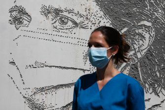 epa08495721 Health worker Raquel Queiros poses in front of her portrait that is part of a mural at Sao Joao Hospital in Porto, Portugal, 19 June 2020. The artwork carved by Portuguese street artist Alexandre Farto, tag-named as VHILS, depicts the faces of ten healthcare workers and is a tribute to all medical and health workers who are looking after those in need amid the ongoing pandemic of the COVID-19 disease caused by the SARS-CoV-2 coronavirus.  EPA/JOSE COELHO