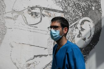 epa08495730 Health worker Sergio Martins poses in front of his portrait that is part of a mural at Sao Joao Hospital in Porto, Portugal, 19 June 2020. The artwork carved by Portuguese street artist Alexandre Farto, tag-named as VHILS, depicts the faces of ten healthcare workers and is a tribute to all medical and health workers who are looking after those in need amid the ongoing pandemic of the COVID-19 disease caused by the SARS-CoV-2 coronavirus.  EPA/JOSE COELHO