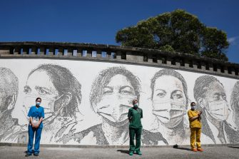 epa08495729 Health workers (L-R), Raquel Queiros, Maria Joao and Idalina Ramos pose in front of their portraits that are part of a mural at Sao Joao Hospital in Porto, Portugal, 19 June 2020. The artwork carved by Portuguese street artist Alexandre Farto, tag-named as VHILS, depicts the faces of ten healthcare workers and is a tribute to all medical and health workers who are looking after those in need amid the ongoing pandemic of the COVID-19 disease caused by the SARS-CoV-2 coronavirus.  EPA/JOSE COELHO