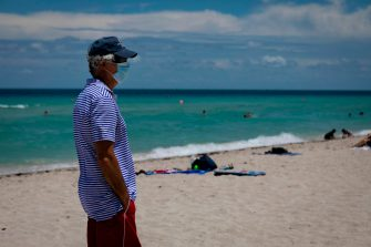 A man is seen at the beach wearing a facemask in Miami Beach, Florida on June 16, 2020. - Florida is reporting record daily totals of new coronavirus cases, but you'd never know it looking at the Sunshine State's increasingly busy beaches and hotels. (Photo by Eva Marie UZCATEGUI / AFP) (Photo by EVA MARIE UZCATEGUI/AFP via Getty Images)