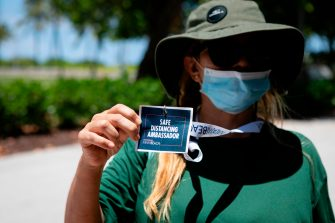 """A Miami Beach worker shows her badge as """"Safe Distancing Ambassador"""" at the entrance to the beach in Miami Beach, Florida on June 16, 2020. - Florida is reporting record daily totals of new coronavirus cases, but you'd never know it looking at the Sunshine State's increasingly busy beaches and hotels. (Photo by Eva Marie UZCATEGUI / AFP) (Photo by EVA MARIE UZCATEGUI/AFP via Getty Images)"""