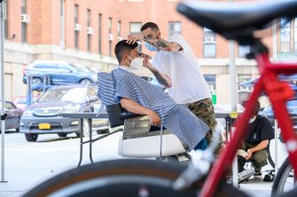 NEW YORK, NEW YORK - JUNE 15: Hairstylist Julian Stull of Frank's Chop Shop gives a free haircut to a medical worker outside Bellevue Hospital on June 15, 2020 in New York City. Hair salons and barber shops remain closed in the city due to the coronavirus (COVID-19) pandemic. (Photo by Noam Galai/Getty Images)