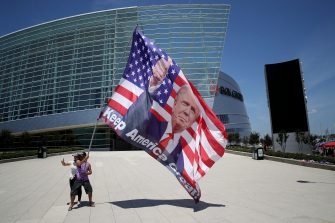TULSA, OKLAHOMA - JUNE 18: Trump supporters pose for photos with a giant Trump flag outside BOK Center, site of U.S. President Donald Trump's first political rally since the start of the coronavirus pandemic, June 18, 2020 in Tulsa, Oklahoma. Trump is scheduled to hold his first political rally at the BOK Center on Saturday while infection rates in the state of Oklahoma continue to rise.  (Photo by Win McNamee/Getty Images)