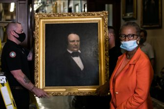 "House Clerk Cheryl Johnson looks on as Architect of the Capitol maintenance workers remove a painting of former confederate speaker James Orr of South Carolina, from the east staircase of the Speakers lobby, on Capitol Hill on June 18, 2020. - House Speaker Nancy Pelosi on June 18 ordered the removal from the US Capitol of four portraits of former lawmakers who served in the Confederacy, saying their images symbolize ""grotesque racism.""  The four outgoing portraits depict 19th century speakers of the House who also served in the Confederacy: Robert Hunter of Virginia, Howell Cobb of Georgia, James Orr of South Carolina, and Charles Crisp of Georgia. (Photo by Graeme Jennings / POOL / AFP) (Photo by GRAEME JENNINGS/POOL/AFP via Getty Images)"