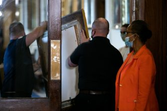 "House Clerk Cheryl Johnson (R) looks on as Architect of the Capitol maintenance workers remove a painting of Howell Cobb of Georgia from the Speaker's Lobby of the US Capitol during the removal of two portraits of Confederate speakers of the House, James Orr and Howell Cobbs, in Washington, DC, on June 18, 2020. - House Speaker Nancy Pelosi on June 18 ordered the removal from the US Capitol of four portraits of former lawmakers who served in the Confederacy, saying their images symbolize ""grotesque racism.""  The four outgoing portraits depict 19th century speakers of the House who also served in the Confederacy: Robert Hunter of Virginia, Howell Cobb of Georgia, James Orr of South Carolina, and Charles Crisp of Georgia. (Photo by Graeme Jennings / POOL / AFP) (Photo by GRAEME JENNINGS/POOL/AFP via Getty Images)"