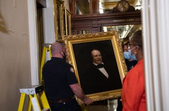 "House Clerk Cheryl Johnson looks on as Architect of the Capitol maintenance workers remove a painting of former confederate speaker James Orr of South Carolina, from the east staircase of the Speakers lobby, on Capitol Hill on June 18, 2020. - House Speaker Nancy Pelosi on June 18 ordered the removal from the US Capitol of four portraits of former lawmakers who served in the Confederacy, saying their images symbolize ""grotesque racism.""  The four outgoing portraits depict 19th century speakers of the House who also served in the Confederacy: Robert Hunter of Virginia, Howell Cobb of Georgia, James Orr of South Carolina, and Charles Crisp of Georgia. (Photo by Nicholas Kamm / POOL / AFP) (Photo by NICHOLAS KAMM/POOL/AFP via Getty Images)"