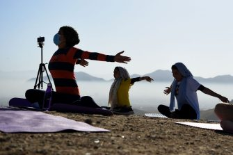 Women perform a yoga posture as they take part in a yoga session at Shahrak Haji Nabi hilltop during International Yoga Day, on the outskirts of Kabul on June 21, 2020. (Photo by WAKIL KOHSAR / AFP) (Photo by WAKIL KOHSAR/AFP via Getty Images)