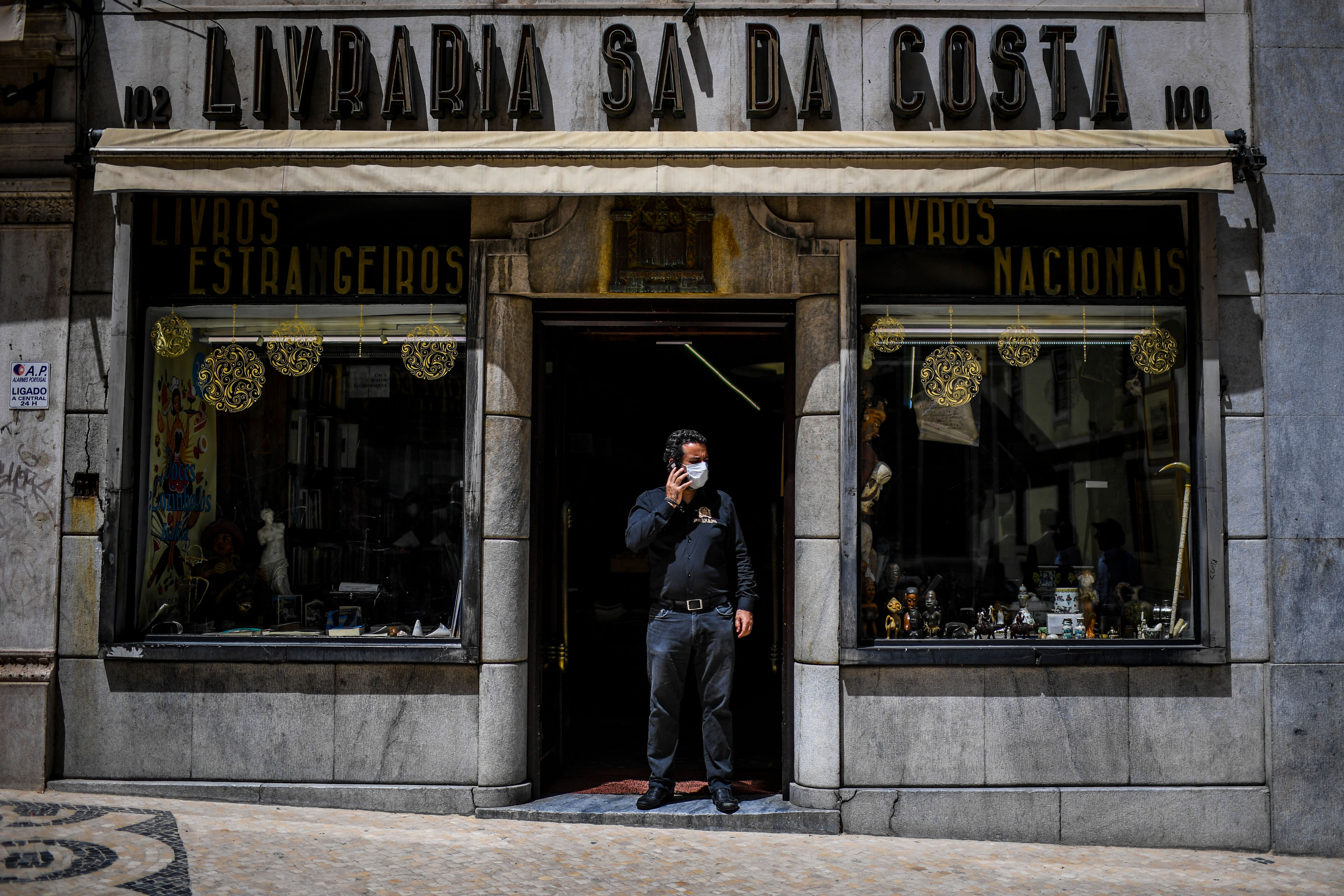 A man speaks on the phone in front of his bookshop in Lisbon on May 4, 2020 as millions of Europeans emerged with relief from coronavirus confinement. - Portugal allowed small shops, hair salons and car dealers to resume business, but ordered face masks to be worn in stores and on public transport. (Photo by PATRICIA DE MELO MOREIRA / AFP) (Photo by PATRICIA DE MELO MOREIRA/AFP via Getty Images)