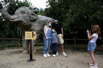 epa08501307 A family wearing a mask takes a photo with a statue of a elephant at the Cali Zoo, Colombia, 21 June 2020. On 21 June and after being closed for more than three months, the Cali Zoo is the first in Latin America to open its doors to the public again in the midst of the COVID-19 pandemic and under the strictest biosecurity measures.  EPA/Pablo Rodriguez