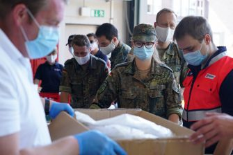 GUETERSLOH, GERMANY - JUNE 23: Soldiers of the Bundeswehr and members of the German Red Cross (DRK) stock up on PPE supplies at a fire department in the village of St. Vit before heading out to take throat swab samples in local communities following a Covid-19 outbreak at the nearby Toennies meat packaging plant during the coronavirus pandemic on June 23, 2020 near Guetersloh, Germany. State authorities announced today they are placing the entire Guetersloh region into lockdown following confirmed Covid-19 infection in over 1,500 employees of the plant. The Bundeswehr, the German armed forces, has stepped in to help test people at the approximately 250 houses and apartment complexes where Toennies employees, many of whom come from Romania, Bulgaria and Poland, live throughout the Guetersloh region. (Photo by Sean Gallup/Getty Images)