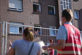 GUETERSLOH, GERMANY - JUNE 23: City employees delivering food and water speak to residents of apartment buildings that house workers from the nearby Toennies meat packing plant who are under quarantine in the town of Verl following a Covid-19 outbreak among Toennies workers during the coronavirus pandemic on June 23, 2020 near Guetersloh, Germany. State authorities announced today they are placing the entire Guetersloh region into semi-lockdown following confirmed Covid-19 infections among over 1,500 employees of the plant. The Bundeswehr, the German armed forces, has stepped in to help test people at the approximately 250 houses and apartment complexes where Toennies employees, many of whom come from Romania, Bulgaria and Poland, live throughout the Guetersloh region. (Photo by Sean Gallup/Getty Images)
