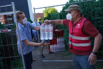 GUETERSLOH, GERMANY - JUNE 23: A city employee delivers food and water to residents of apartment buildings that house workers from the nearby Toennies meat packing plant who are under quarantine in the town of Verl following a Covid-19 outbreak among Toennies workers during the coronavirus pandemic on June 23, 2020 near Guetersloh, Germany. State authorities announced today they are placing the entire Guetersloh region into semi-lockdown following confirmed Covid-19 infections among over 1,500 employees of the plant. The Bundeswehr, the German armed forces, has stepped in to help test people at the approximately 250 houses and apartment complexes where Toennies employees, many of whom come from Romania, Bulgaria and Poland, live throughout the Guetersloh region. (Photo by Sean Gallup/Getty Images)
