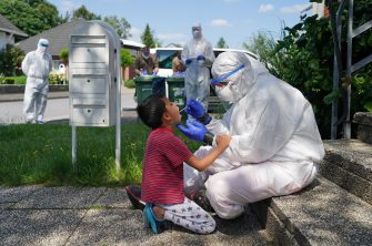 GUETERSLOH, GERMANY - JUNE 23: A worker with the German Red Cross (DRK) dressed in full PPE takes a throat swab sample from local resident Arsalan, 6, in the village of St. Vit following a Covid-19 outbreak at the nearby Toennies meat packaging center during the coronavirus pandemic on June 23, 2020 near Guetersloh, Germany. State authorities announced today they are placing the entire Guetersloh region into lockdown following confirmed Covid-19 infection in over 1,500 employees of the plant. The Bundeswehr, the German armed forces, has stepped in to help test people at the approximately 250 houses and apartment complexes where Toennies employees, many of whom come from Romania, Bulgaria and Poland, live throughout the Guetersloh region. (Photo by Sean Gallup/Getty Images)