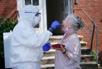 GUETERSLOH, GERMANY - JUNE 23: A doctor with the German Red Cross (DRK) dressed in full PPE takes a throat swab sample from a local resident, who said she did not mind being photographed, in the village of St. Vit following a Covid-19 outbreak at the nearby Toennies meat packaging center during the coronavirus pandemic on June 23, 2020 near Guetersloh, Germany. State authorities announced today they are placing the entire Guetersloh region into lockdown following confirmed Covid-19 infection in over 1,500 employees of the plant. The Bundeswehr, the German armed forces, has stepped in to help test people at the approximately 250 houses and apartment complexes where Toennies employees, many of whom come from Romania, Bulgaria and Poland, live throughout the Guetersloh region. (Photo by Sean Gallup/Getty Images)