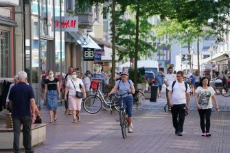 GUETERSLOH, GERMANY - JUNE 24: People stroll in the city center on the Berliner Strasse shopping street during a semi-lockdown following a Covid-19 outbreak at the nearby Toennies meat packaging center on June 24, 2020 in Guetersloh, Germany. Over 1,500 employees of the plant have been confirmed to be infected and authorities have brought in the semi-lockdown, which forces bars, gyms and indoor sports halls to close though allows shops and restaurants to remain open, to stem a further spread of the virus. The Bundeswehr, the German armed forces, has stepped in to help test people at the approximately 250 houses and apartment buildings where Toennies employees, many of whom come from Romania, Bulgaria and Poland, live throughout the Guetersloh region. (Photo by Sean Gallup/Getty Images)