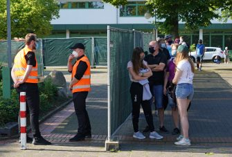 GUETERSLOH, GERMANY - JUNE 24: People wait in line to be tested for Covid-19 infection following a Covid-19 outbreak at the nearby Toennies meat packaging center during the coronavirus pandemic on June 24, 2020 in Guetersloh, Germany. The line at the Carl Miele vocational school, which is being used a Covid testing site, stretched approximately one kilometer long. Many of those waiting are hoping to go on vacation abroad soon and are concerned they will need certification of being free of infection. Over 1,500 employees of the plant have been confirmed to be infected and authorities are racing to stem a further spread of the virus. The Bundeswehr, the German armed forces, has stepped in to help test people at the approximately 250 houses and apartment buildings where Toennies employees, many of whom come from Romania, Bulgaria and Poland, live throughout the Guetersloh region. (Photo by Sean Gallup/Getty Images)