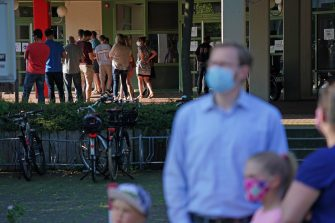 GUETERSLOH, GERMANY - JUNE 24: People wait in a snaking line to be tested for Covid-19 infection following a Covid-19 outbreak at the nearby Toennies meat packaging center on June 24, 2020 in Guetersloh, Germany. The line at the Carl Miele vocational school, which is being used a Covid testing site, stretched approximately one kilometer long. Many of those waiting are hoping to go on vacation abroad soon and are concerned they will need certification of being free of infection. Over 1,500 employees of the plant have been confirmed to be infected and authorities are racing to stem a further spread of the virus. The Bundeswehr, the German armed forces, has stepped in to help test people at the approximately 250 houses and apartment buildings where Toennies employees, many of whom come from Romania, Bulgaria and Poland, live throughout the Guetersloh region. (Photo by Sean Gallup/Getty Images)