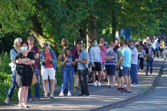 GUETERSLOH, GERMANY - JUNE 24: People wait in a line approximately one kilometer long to be tested for Covid-19 infection at the Carl Miele vocational school following a Covid-19 outbreak at the nearby Toennies meat packaging center on June 24, 2020 in Guetersloh, Germany. Many of those waiting are hoping to go on vacation abroad soon and are concerned they will need certification of being free of infection. Over 1,500 employees of the plant have been confirmed to be infected and authorities are racing to stem a further spread of the virus. The Bundeswehr, the German armed forces, has stepped in to help test people at the approximately 250 houses and apartment buildings where Toennies employees, many of whom come from Romania, Bulgaria and Poland, live throughout the Guetersloh region. (Photo by Sean Gallup/Getty Images)