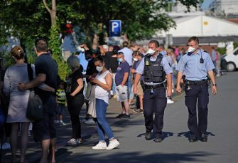 GUETERSLOH, GERMANY - JUNE 24: Police walk past a line of people waiting to be tested for Covid-19 infection following a Covid-19 outbreak at the nearby Toennies meat packaging center on June 24, 2020 in Guetersloh, Germany. The line at the Carl Miele vocational school, which is being used a Covid testing site, stretched approximately one kilometer long. Many of those waiting are hoping to go on vacation abroad soon and are concerned they will need certification of being free of infection. Over 1,500 employees of the plant have been confirmed to be infected and authorities are racing to stem a further spread of the virus. The Bundeswehr, the German armed forces, has stepped in to help test people at the approximately 250 houses and apartment buildings where Toennies employees, many of whom come from Romania, Bulgaria and Poland, live throughout the Guetersloh region. (Photo by Sean Gallup/Getty Images)