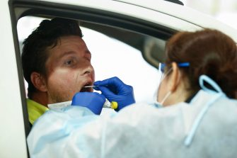 epa08507652 A man undergoes a swab test at a drive-thru COVID-19 testing facility at the Melbourne Showgrounds in Melbourne, Australia, 25 June 2020. The Australian Defence Force (ADF) and other states have been called in to help Victoria tackle its rising number of coronavirus cases.  EPA/DANIEL POCKETT AUSTRALIA AND NEW ZEALAND OUT