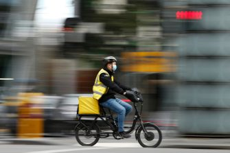 epa08507667 A photo taken using a slow shutter speed shows a delivery rider wearing a face mask in Melbourne, Australia, 25 June 2020. The Australian Defence Force (ADF) and other states have been called in to help Victoria tackle its rising number of coronavirus cases.  EPA/DANIEL POCKETT AUSTRALIA AND NEW ZEALAND OUT