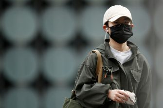epa08507658 A person wearing a mask walk around Melbourne, Australia, 25 June 2020. The Australian Defence Force (ADF) and other states have been called in to help Victoria tackle its rising number of coronavirus cases.  EPA/DANIEL POCKETT AUSTRALIA AND NEW ZEALAND OUT