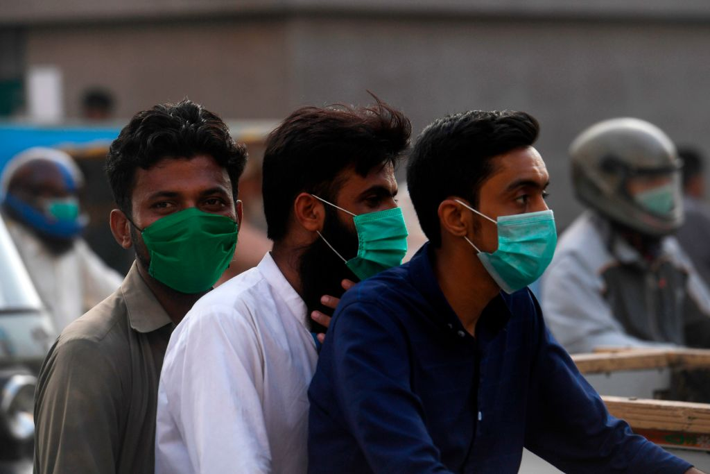 Commuters wearing facemasks ride on a bike on a street in Karachi on June 22, 2020 as the COVID-19 coronavirus cases continue to rise. (Photo by Asif HASSAN / AFP) (Photo by ASIF HASSAN/AFP via Getty Images)