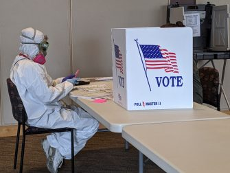 Elections Chief Inspector Mary Magdalen Moser runs a polling location in Kenosha, Wisconsin, in full hazmat gear as the Wisconsin primary kicks off despite the coronavirus pandemics on April 7, 2020. - Voters in Wisconsin began casting ballots Tuesday in a controversial presidential primary held despite a state-wide, stay-at-home order and concern that the election could expose thousands of voters and poll workers to the coronavirus. Democratic officials had sought to postpone the election but were overruled by the top state court, and the US Supreme Court stepped in to bar an extension of voting by mail that would have allowed more people to cast ballots without going to polling stations. Both courts have conservative majorities. (Photo by Derek R. HENKLE / AFP) (Photo by DEREK R. HENKLE/AFP via Getty Images)