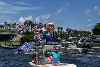TOPSHOT - Supporters of US President Donald Trump wave flags as they participates in a boat rally to celebrate Donald Trump's birthday in Fort Lauderdale, Florida on June 14, 2020. (Photo by CHANDAN KHANNA / AFP) (Photo by CHANDAN KHANNA/AFP via Getty Images)